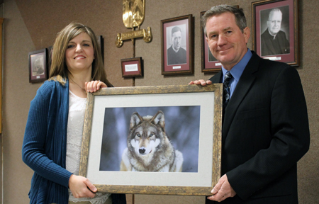 LINCOLN, CATHEDRAL - Joel Sartore of the Cathedral of the Risen Christ in Lincoln, a freelance photographer for National Geographic, presents a print to Laura Johnson, chair of the Cathedral School auction. The print is one of four that will be included among the auction items at the Feb. 1 event to support the school. (SNR photo by Cathy Blankenau Bender)